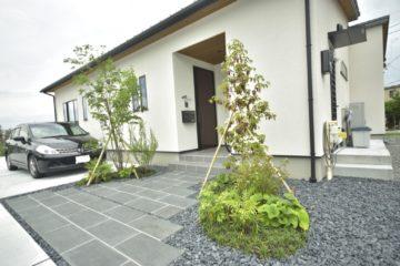 広い駐車場と石張りのアプローチのあるお庭